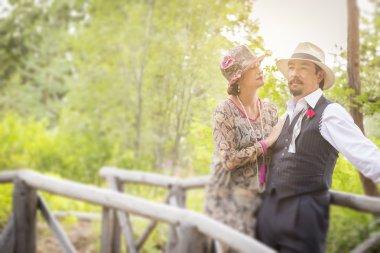 1920s Dressed Romantic Couple on Wooden Bridge