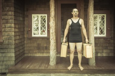 Gentleman Dressed in 1920s Era Swimsuit Holding Suitcases on