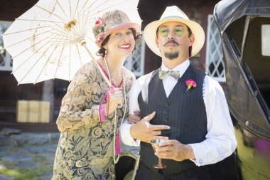 Mixed-Race Couple Dressed in 1920s Era Fashion Sipping Champa