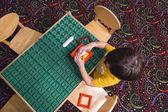 Rezsi játékai az asztalnál játszó fiú