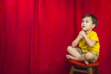 Mixed Race Boy Sitting on Stool in Front of Curtain