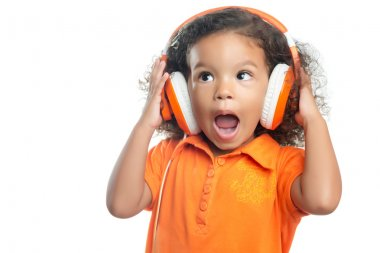 Excited little girl with an afro hairstyle enjoying her music on bright orange headphones