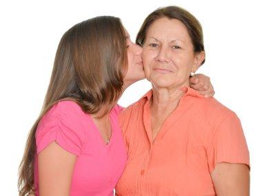Hispanic teenage girl kissing her grandmother