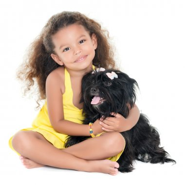 Small hispanic girl hugging her pet dog