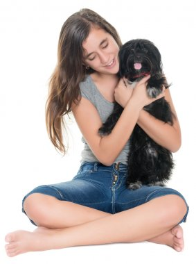 Pretty teenage girl hugging her pet dog