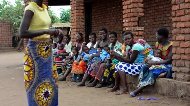 Ismeretlen nők, akik Nanjiriben hallgatják az egészségügyi dolgozók előadását Lilongwe külvárosában, Malawiban, 2020. december 19.