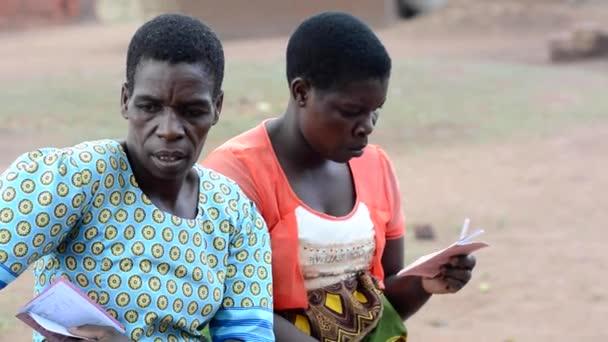 Azonosítatlan nők kint ülnek és hallgatják az egészségügyi dolgozók előadását Nanjiriben, Lilongwe külvárosában, Malawi, 2020. december 19.