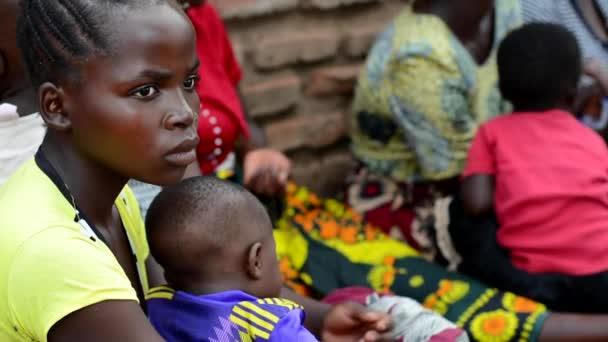 Ismeretlen nők, akik arra várnak, hogy gyermekeik súlyát megmérjék Nanjiriben, Lilongwe külvárosában, Malawiban, 2020. december 19.