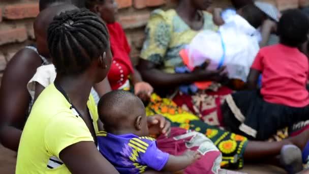 Neidentifikované ženy, které čekají na měření hmotnosti svých dětí v Nanjiri na předměstí Lilongwe, Malawi, 19. prosince 2020
