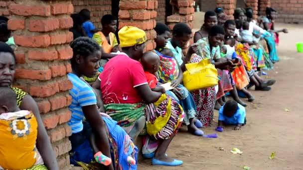 Unbekannte Frauen warten in Nanjiri, am Stadtrand von Lilongwe, Malawi, darauf, das Gewicht ihrer Kinder messen zu lassen, 19. Dezember 2020