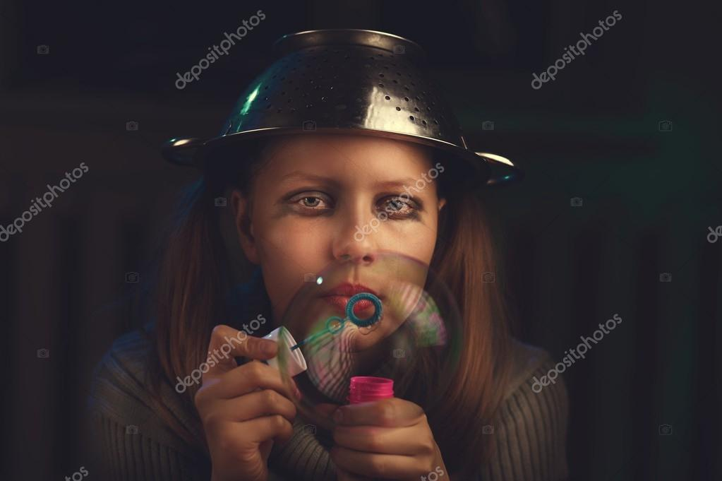 Sad teen girl sits and blows soap bubbles