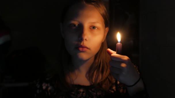 Dospívající dívka se svíčkou, strach na tváři