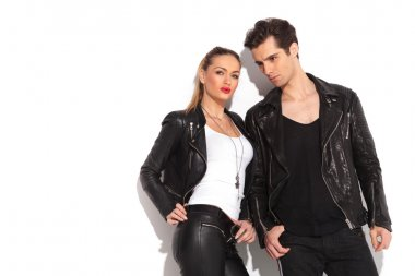 young fashion couple in leather clothes posing in studio