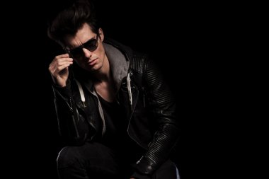 young fashion model in leather jacket taking off his sunglasses