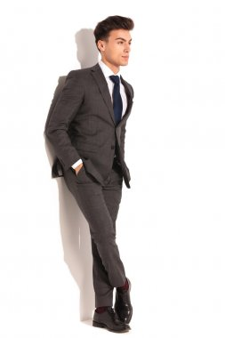 business man with hands in pockets and legs crossed