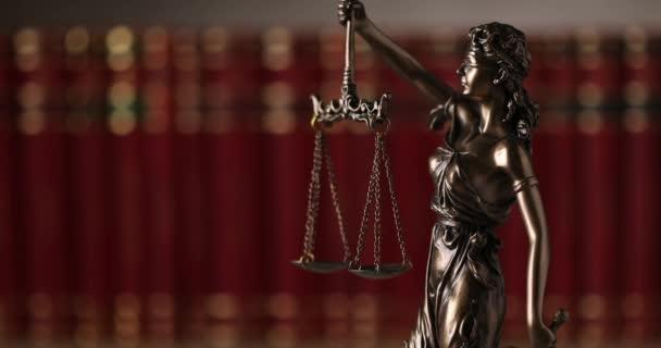 nemzetközi bronz jelképe jog által képviselt bekötött szemmel istennő kezében egyensúlyt jelképező két széles jogforrás, pártatlanság és a hatalom, forog lassan az egyetemi szobában a háttérben készült könyvek