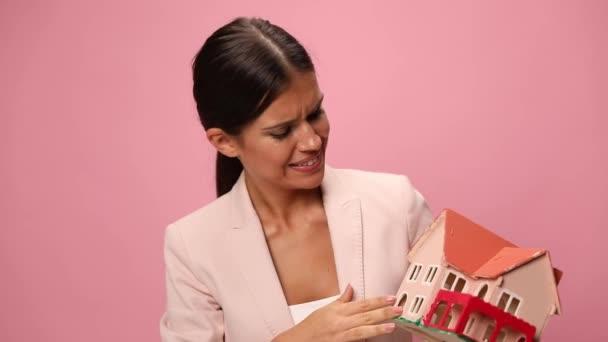 podnikatelka v růžovém obleku drží a ukazuje model domu, přikyvuje, usmívá se a ukazuje prstem na růžové pozadí