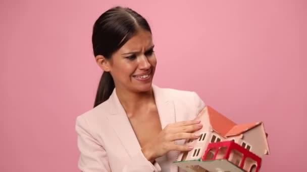 junge Frau im rosafarbenen Anzug mit Baumodell, lächelnd und Daumen hoch gestikulierend auf rosa Hintergrund