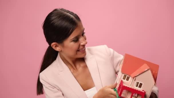 glückliche junge Geschäftsfrau im rosa Anzug, die ein Hausmodell hält und empfiehlt, nickt zustimmend auf rosa Hintergrund