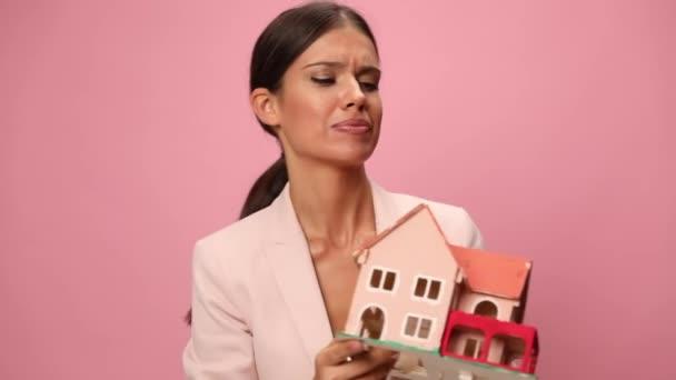 glückliche Frau im rosafarbenen Anzug, die ein Baumodell empfiehlt, die Faust in die Luft reckt und auf rosa Hintergrund jubelt
