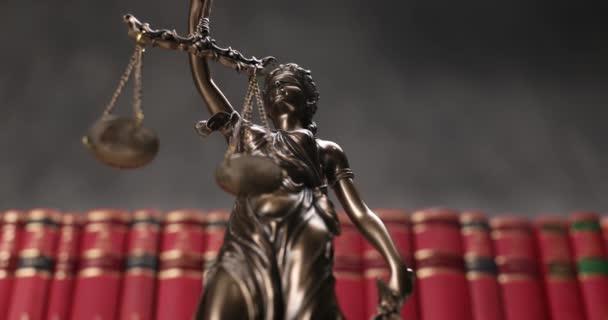 bronz jogi szobor, amelyet bekötött szemű istennő forgat, és amely pártatlanságot és két széles jogforrást jelöl, könyvek hátterével