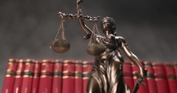termék videó a nemzetközi bronz szimbólum a jog által képviselt bekötött szemű istennő, amely egyensúlyt jelöl két széles jogforrás, pártatlanság és a hatalom, forog lassan előtt sor piros könyvek