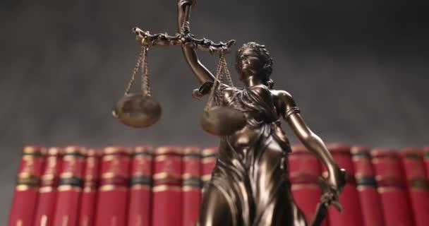 bronz bekötött szemű istennő jogi szoborforgatás, kezében egy skála és kard szimbolizálja pártatlanság és két széles jogforrás egy egyetemi szobában háttérrel készült piros könyvek sorban