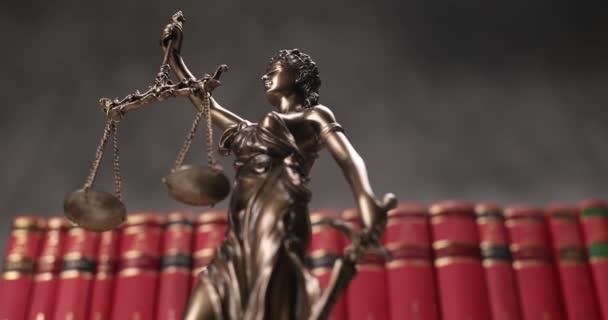 igazságszolgáltatás szobor által képviselt bekötött szemmel hölgy kezében egyensúly és a kard jelképezi erő és pártatlanság, forgó előtt piros könyvek