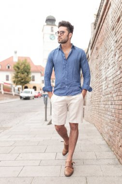 Young casual man walking and looks to side