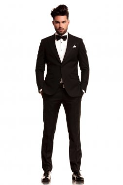 Man wearing tuxedo standing with hands in pockets