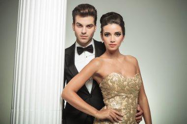 fashion elegant couple man in tuxedo and woman near column