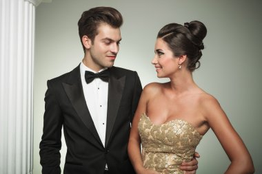 man in tuxedo embracing his woman and smiles