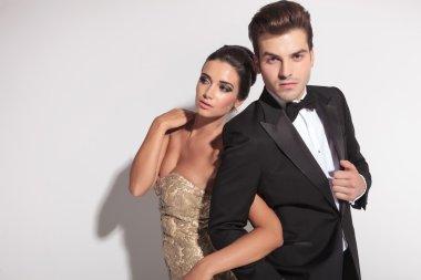 Elegant couple posing, holding each other arm.
