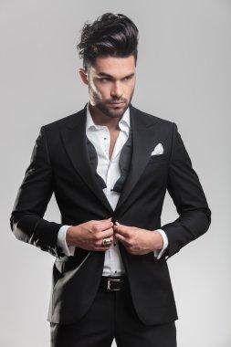 young man wearing tuxedo closing his jacket