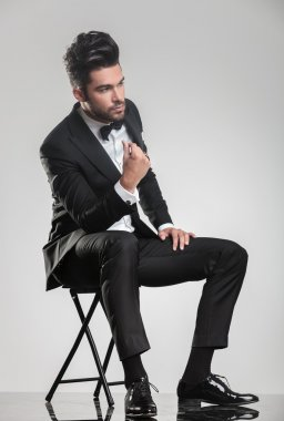 man in tuxedo sitting on a stool snapping his finger