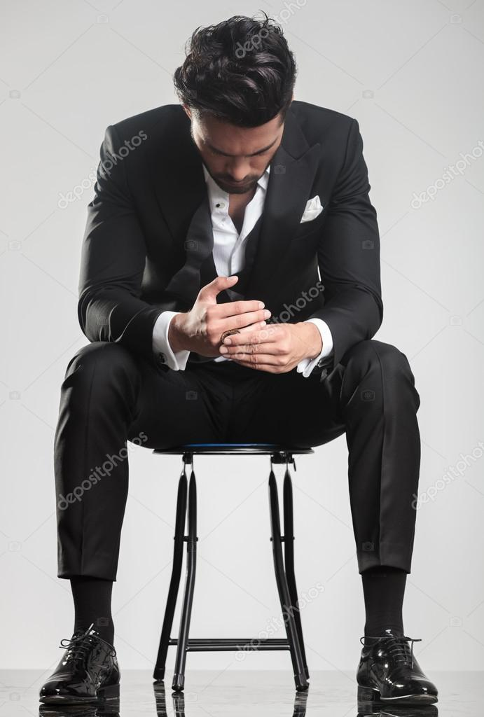 man in tuxedo looking down while sitting on a stool,