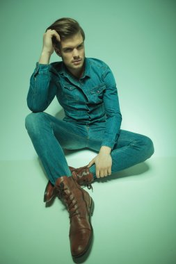 young fashion man sitting on the floor, fixing his hair