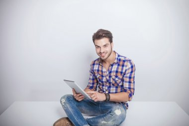 young fashion man holding a tablet pad computer.