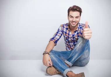 Young man smiling while showing the thumbs up gesture.