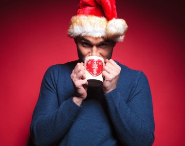 Young santa man drinking a hot tea