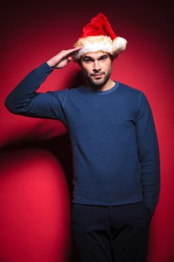 young santa wearing a blue sweater saluting