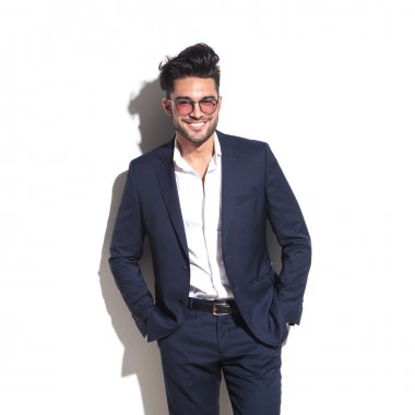 Smiling business man leaning on a white wall