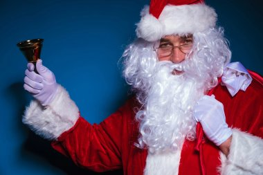 Santa Claus holding a bell in his right hand