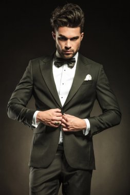 Young elegant business man arranging his tuxedo.