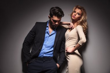man looking down while his girlfriend is leaning on him