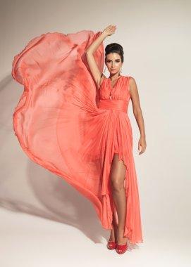 elegant fashion woman fluttering her coral dress