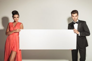 Fashion man and woman holding a blank board.