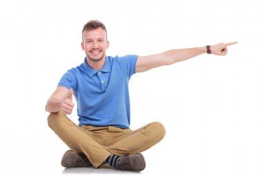 seated young casual man points to side