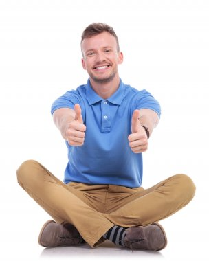 seated young casual man shows thumbs up