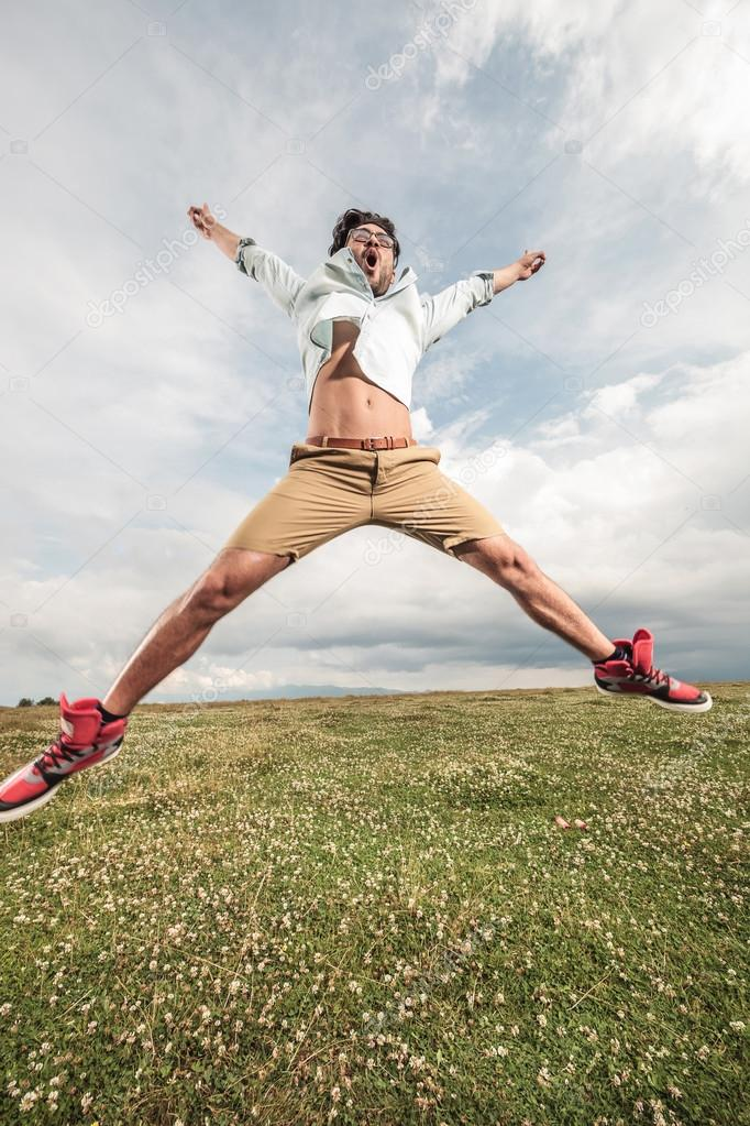 Young man jumping on a field full of flowers
